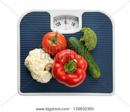 Bathroom scale with vegetables on white background