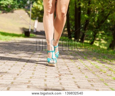 female feet in green shoes are on the sidewalk on summer day closeup