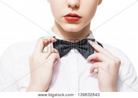 Close up portrait of a young woman in a white shirt and bow tie with red lipstick  on a white background