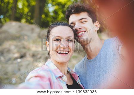 Happy loving couple of teenagers smiling. Cheerful hipsters making a selfie outdoors. Young couple making a selfie outdoors.