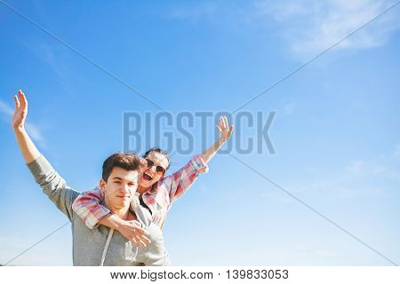 Teenager boy giving piggy back to his girlfriend. Piggyback couple on blue sky background.