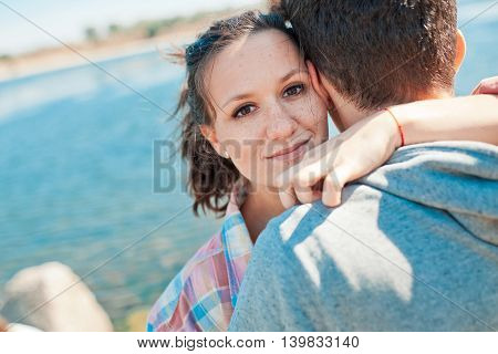 Teenage girl hugging young man and looking to the camera on a lake background. Embracing couple