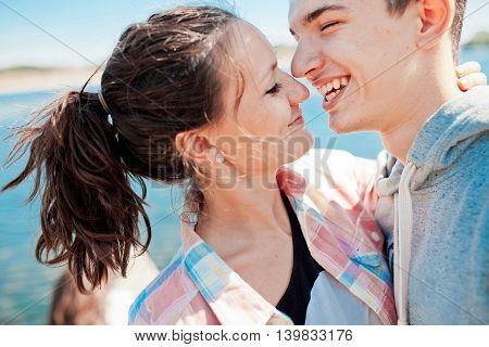 Teenage loving couple kissing. Hipsters love. Young woman kisses his boyfriend