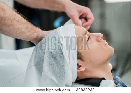 Hairstylist washing client's hair in barber shop.