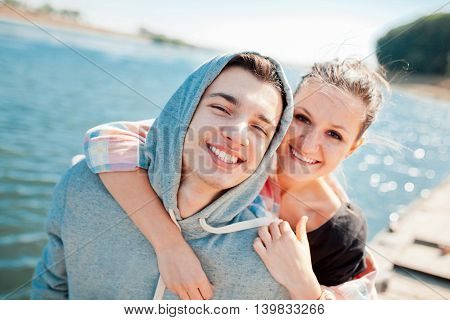 Teenage loving couple hugging. Hipsters love. Young woman hugging his boyfriend from behind. Happy teenage girl standing behind young man.