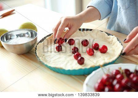 Female hands cooking cherry pie in kitchen