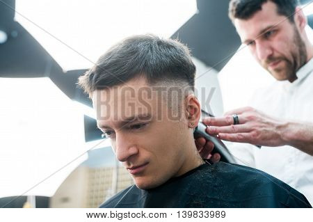 Professional styling. Close up side view of young man getting haircut by hairdresser with electric razor at barbershop.