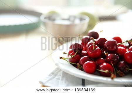Juicy cherries in white plate on striped napkin