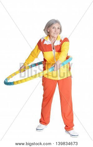 Senior woman exercising with hoop  on white background