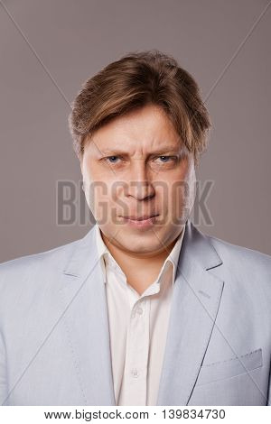 Angry Frowning Middle Age Man in Blue Jacket, isolated over grey background.