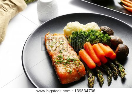 Tasty dish with baby carrots and salmon on black plate closeup