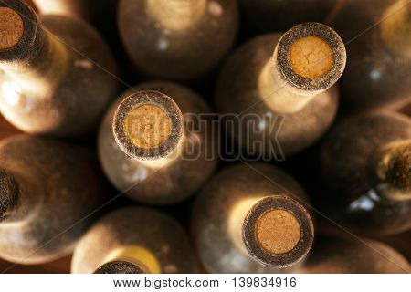 Stacks of dusty wine bottles on wooden background, upside view. Close up