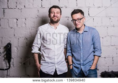 Two young men startupers over grey brick wall loft interior design.