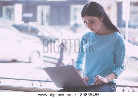 Hardworking one. Busy and serious young woman sitting on a window sill and using laptop while being in a cafe