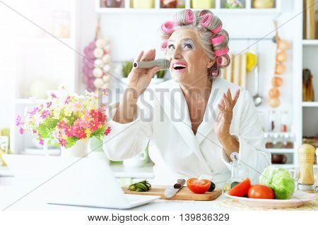 Senior woman in  hair rollers at kitchen with laptop and vegetables