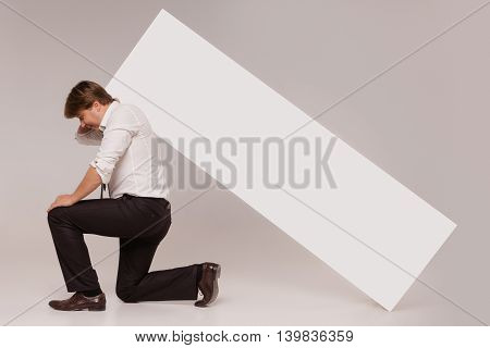 Kneeled businessman holds blank copy space banner on his back isolated on grey.