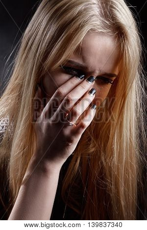 sad young woman crying covering her face