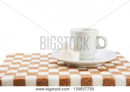 Empty coffee cup on a saucer with three cubes of sugar on a stand of white and brown sugar. Isolated on white.