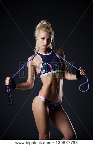 Fitness woman posing with skipping rope on a black background. Sports motivation. Perfect female fit figure. Sexy girl in the studio