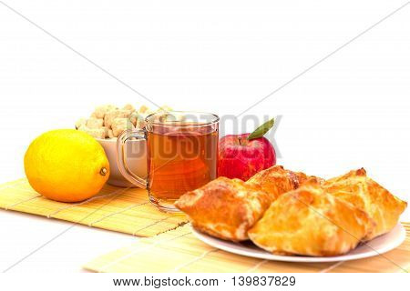 mug of tea cakes on a plate lemon apple with green leaf and sugar in a bowl on a bed of reeds. Isolated on white background.