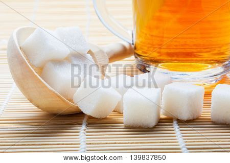 cup of tea and sugar in a wooden spoon on the mat. Isolated on white.
