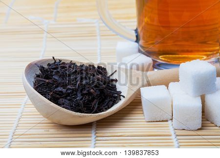 black tea in a wooden spoon sugar cubes and a mug of black tea on the mat.