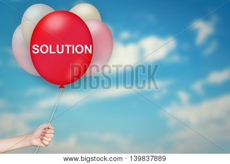 Hand Holding solution Balloon with sky blurred background