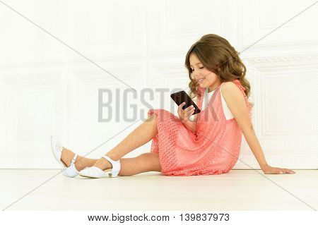 portrait of cute little girl  in beautiful dress with mobile phone