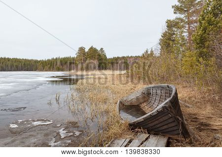 Old broken boat on the coast of river on a cloudy day. Spring Karelia.