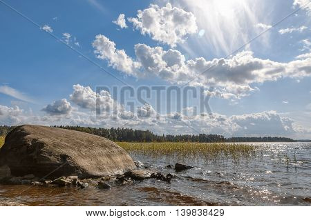 Lake with a large stone on a sunny day. Landscape with nobody.