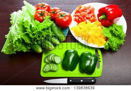 Halved peppers and a knife on a cutting board. Sliced cucumber tomato pepper. Lettuce. Vegetables in the dishes.