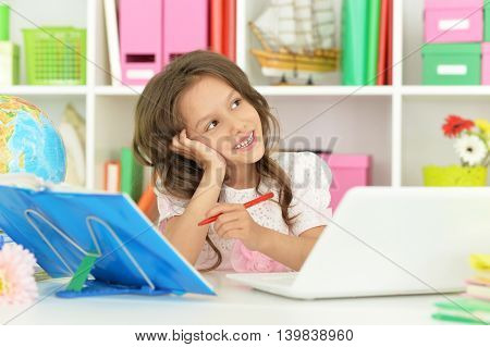 Cute  student girl  with book, globe and laptop at class