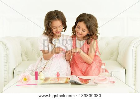 Cute   girls with magazine and cosmetics  at home