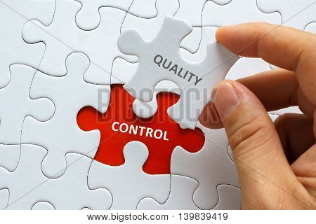 Hand Holding Piece Of Jigsaw Puzzle With Word Quality Control.