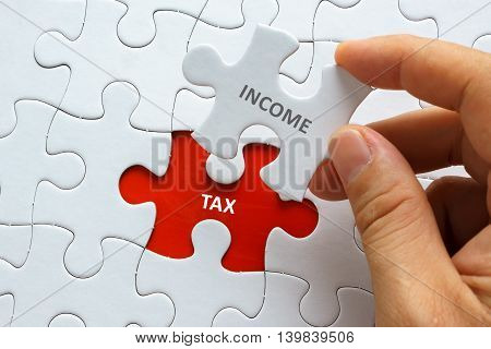 Hand Holding Piece Of Jigsaw Puzzle With Word Income Tax.