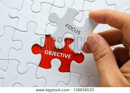 Hand Holding Piece Of Jigsaw Puzzle With Word Focus Objective.