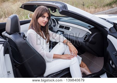 girl sitting in a white cabriolet with open door