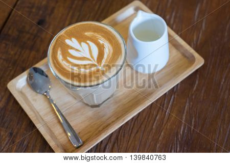 Hot Piccolo latte coffee serve with syrup in wood tray on wooden table.