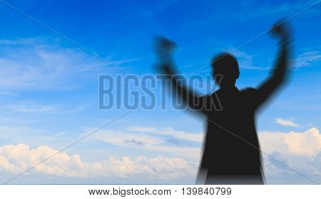 Motion blurred of Silhouette man showing his hand on blue sky background, Successful business concept.