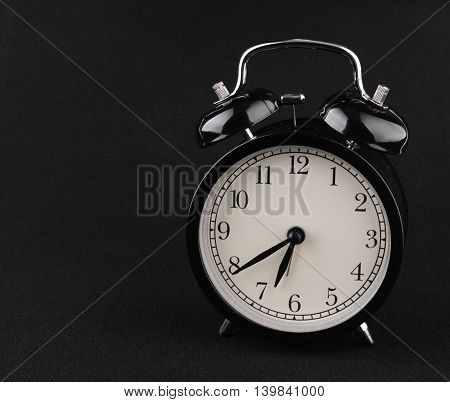 Black alarm clock on black textile background