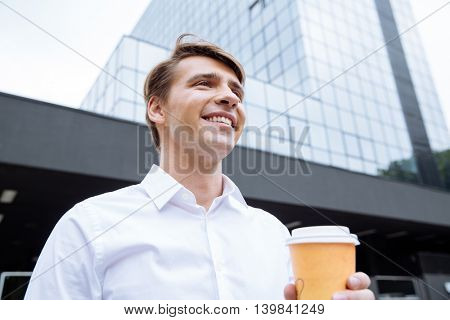 Happy confident young businessman standing near skyscraper and drinking coffee