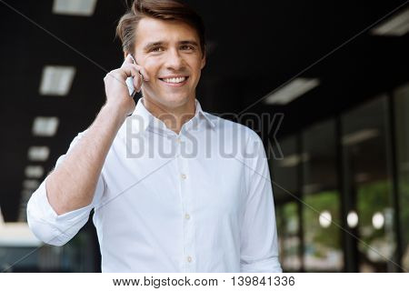 Cheerful young businessman smiling and talking on cell phone on the street