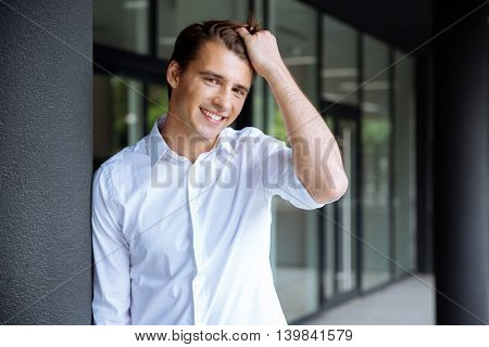 Cheerful confident young businessman standing and smiling near business center