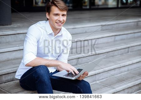 Happy attractive young man sitting outdoors and using laptop