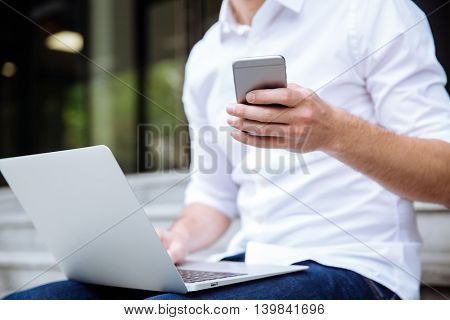 Closeup of young businessman in white shirt working with laptop and smartphone outdoors