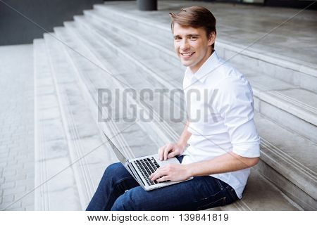 Smiling confident young man sitting on stairs and using laptop outdoors