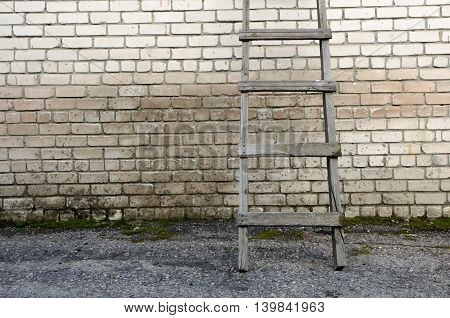 Old wooden ladder against a wall brick