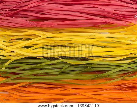 Wheat multicolored noodles italian raw pasta background