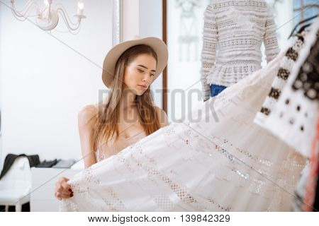 Pensive pretty young woman in hat standing and choosing skirt in clothing store