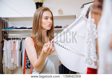 Serious thoughtful young woman doing shopping in the shop